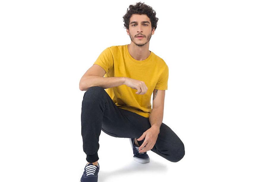 modelo veste calça de moletom t-shirt-básica mostarda tênis