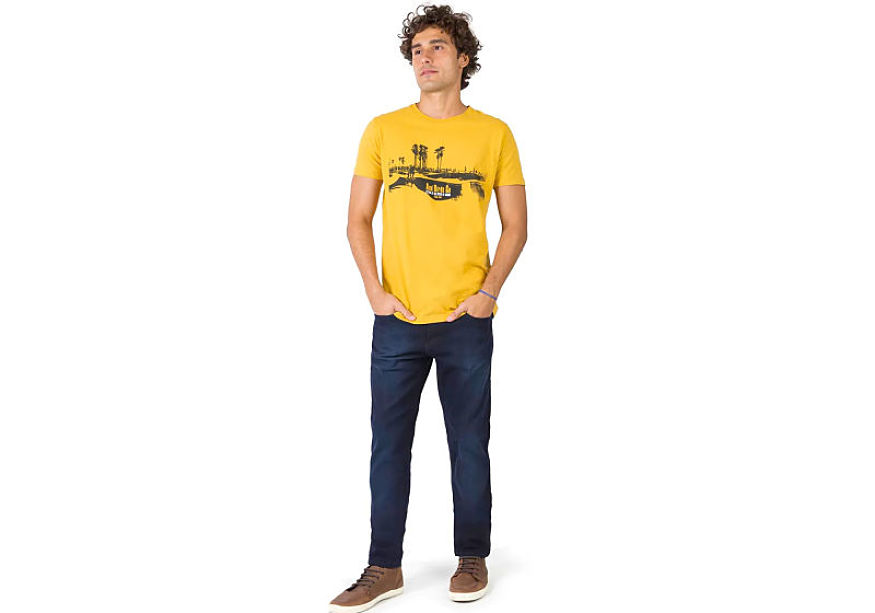modelo veste t-shirt estampada amarela calça jeans lavagem escura com tênis