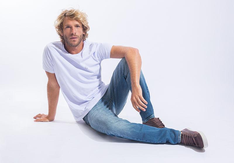 modelo veste calça jeans e t-shirt branca sentado no chão