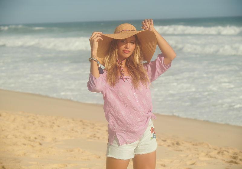 modelo na praia de bata rosa short branco e chapéu