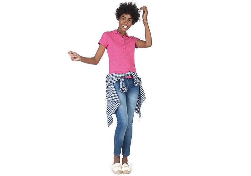 modelo veste calça jeans cigarrete polo rosa com camisa xadrez amarrada na cintura