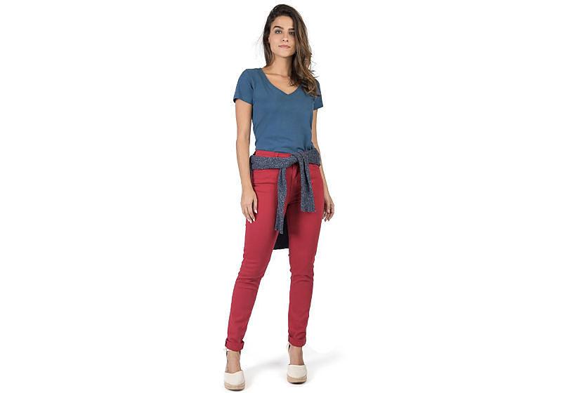 modelo veste calça vermelha blusa estampada com casaco amarrado na cintura