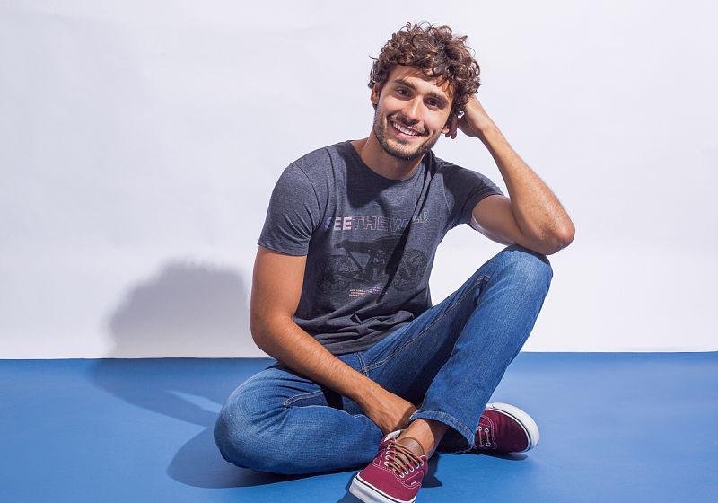 modelo sentado no chão veste calça skinny t-shirt estampada tênis vinho
