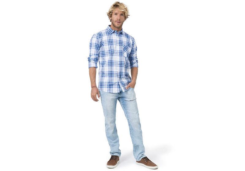 modelo veste camisa xadrez branca e azul e calça jeans  clara com tênis
