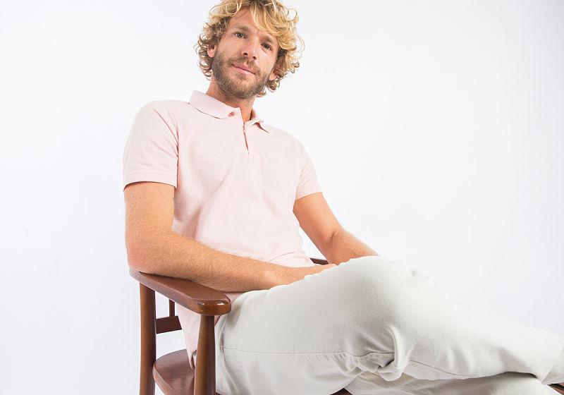 modelo sentado na cadeira com blusa polo rosa e calça chino
