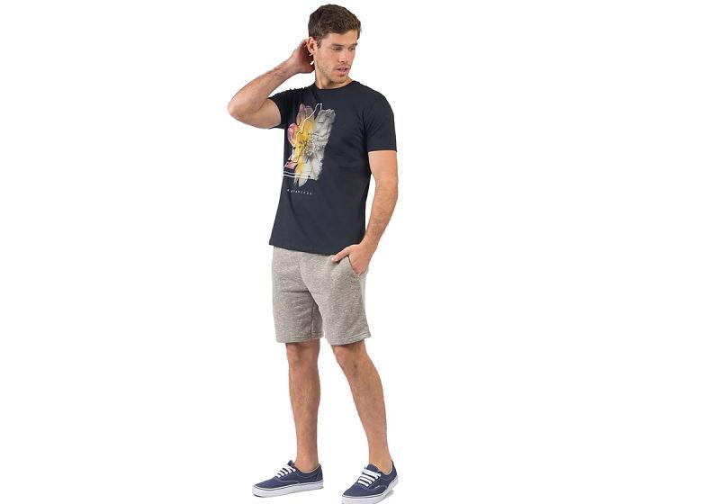 modelo veste t-shirt estampada preta e bermuda jogger verde militar