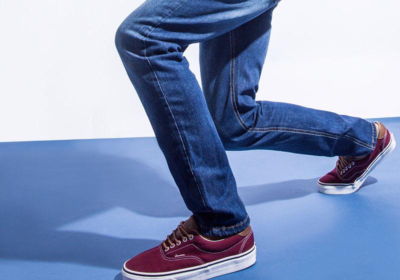 calça jeans skinny e tênis vinho em um fundo branco e azul