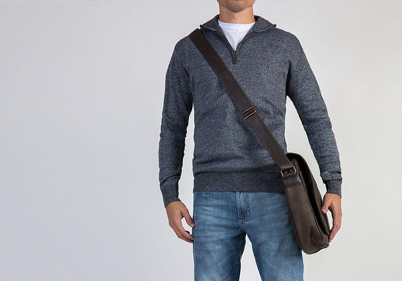 homem com suéter de ziper tshirt branca calça jeans e bolsa carteiro