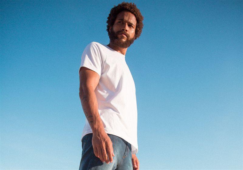 Homem moreno de camiseta branca e calça jeans