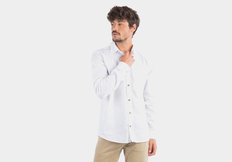 Homem em pé de camisa branca e calça bege