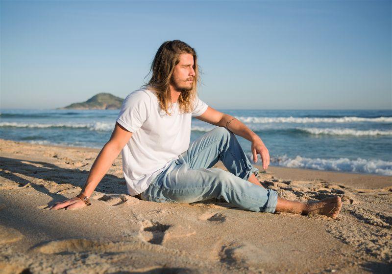 Homem sentado na areia em uma praia, de camiseta branca e calça jeans