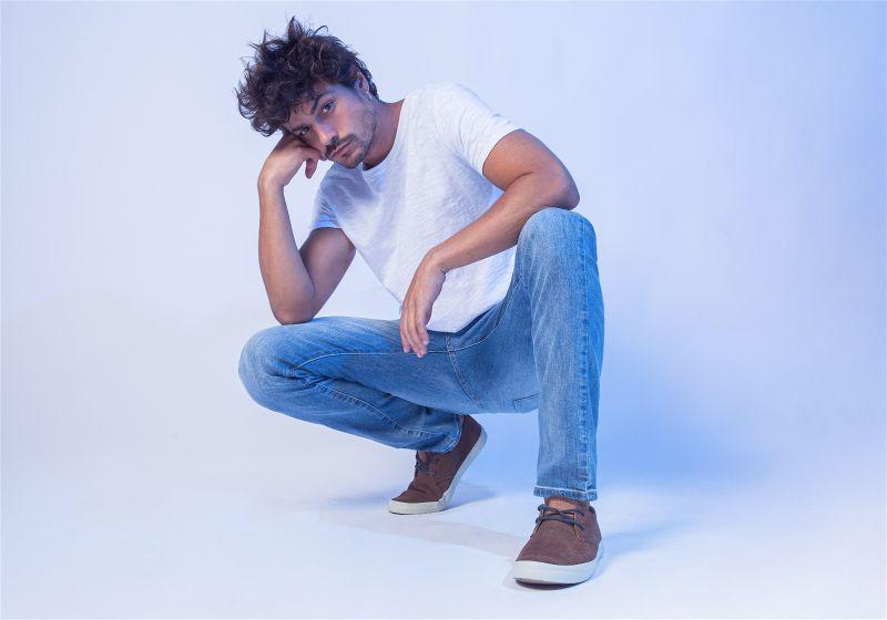 Homem em pose agachado  com camiseta branca e calça jeans