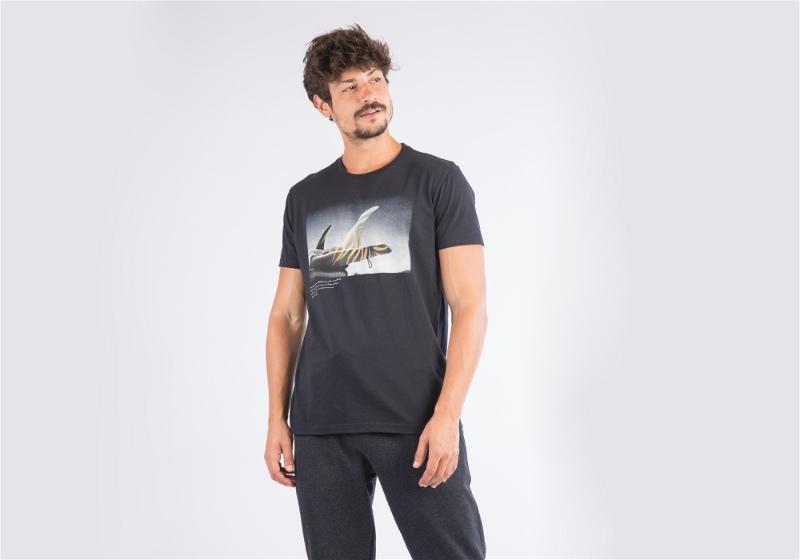 Homem em pé com calça e camiseta preta