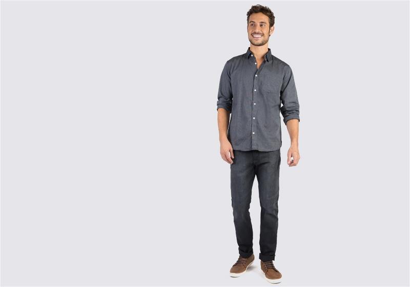 Homem em pé de calça jeans escura e camisa cinza