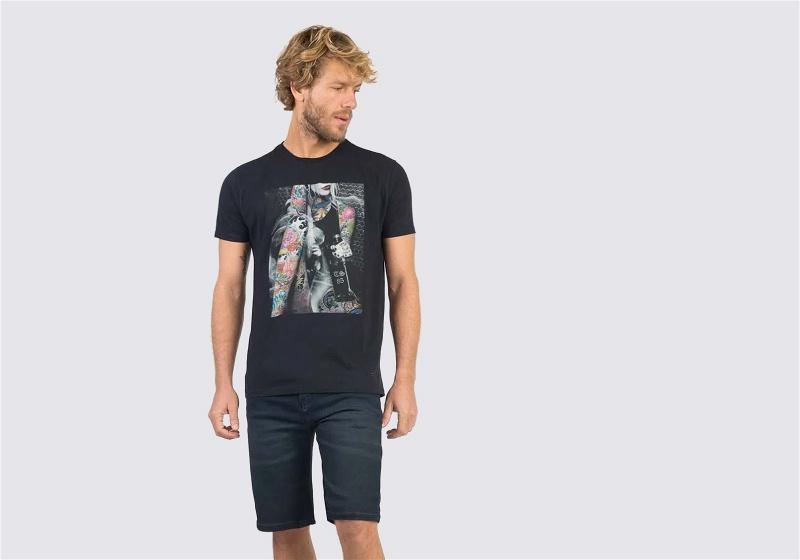 Homem em pé de bermuda jeans escura e camiseta preta
