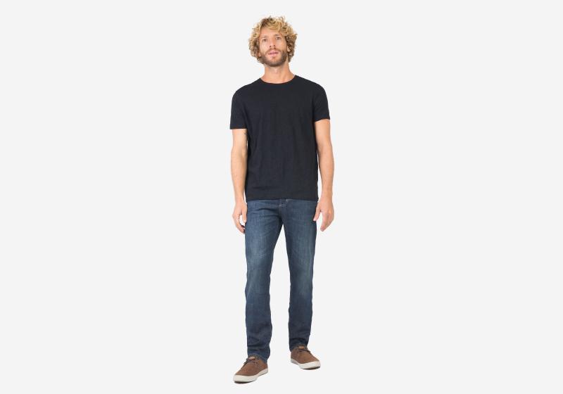 Homem em pé utilizando camiseta preta e calça jeans escura