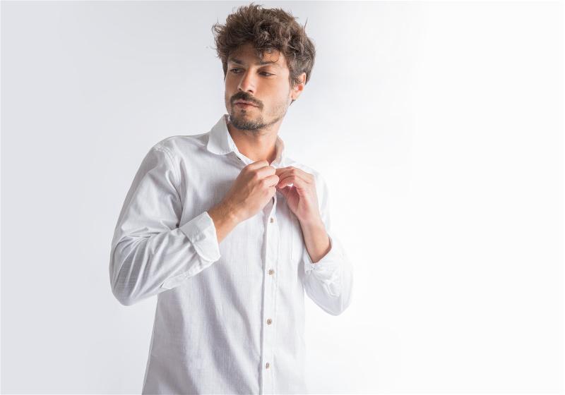 Homem utilizando camisa branco, fechando botão