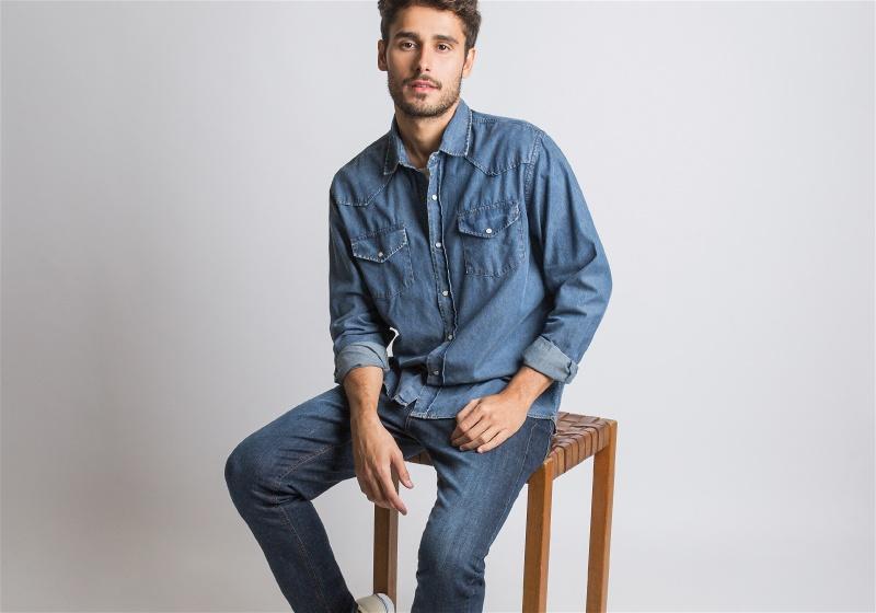 Homem sentado utilizando camisa e calça jeans
