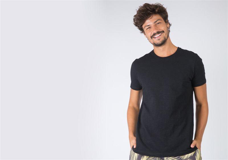 Homem em pé utilizando camiseta preta, com as mãos no bolso da bermuda