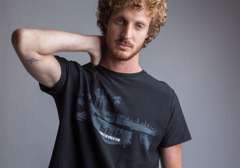 Homem de camiseta preta, fazendo pose com a mão na nuca