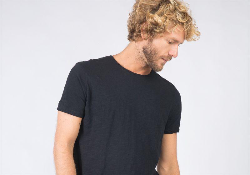 Homem de camiseta preta olhando para baixo